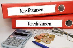 2 Ordner zu Kreditzinsen mit Taschenrechner und Kleingeld